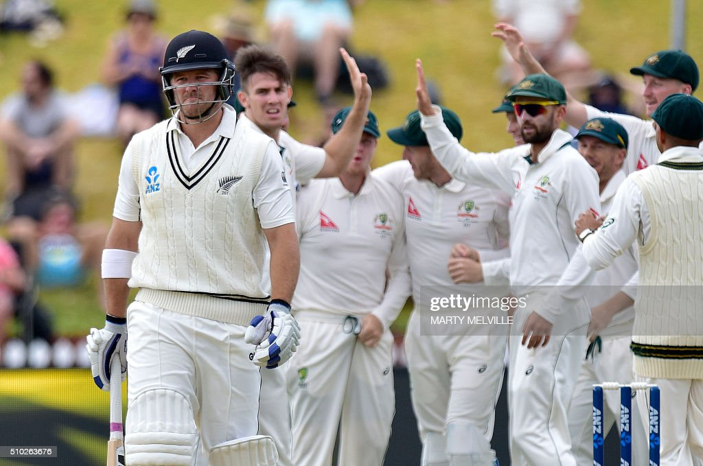 New Zealand's Corey Anderson (L) walks from the field after being caught with LBW as Australia celebrate during day four of the first cricket Test match between New Zealand and Australia at the Basin Reserve in Wellington on February 15, 2016. / AFP / Marty Melville