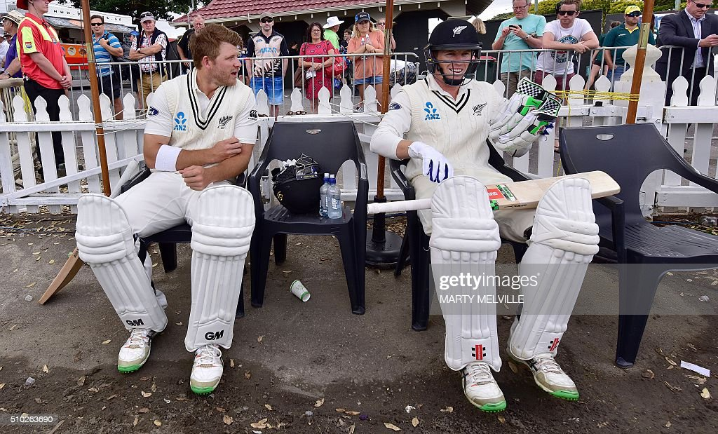 New Zealand's Corey Anderson (L) with team mate Henry Nicholls wait for the start of the days play during day four of the first cricket Test match between New Zealand and Australia at the Basin Reserve in Wellington on February 15, 2016. / AFP / Marty Melville