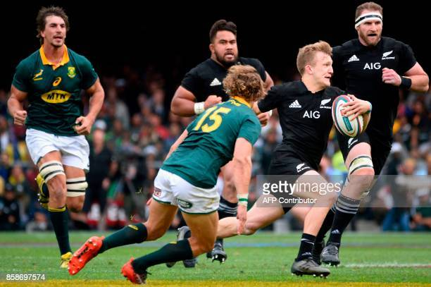 New Zealand's Damian Mckenzie runs with the ball on his way to score a try during the Rugby test match between South Africa and New Zealand at...