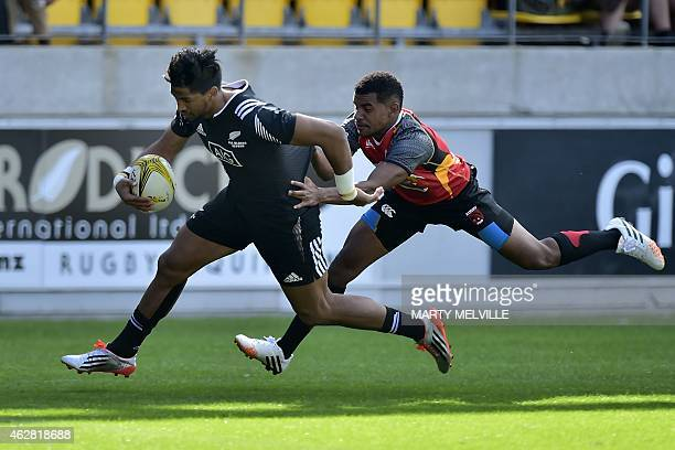 New Zealand's Dylan Collier runs in a try as he is tackled by Papua New Guinea's Terence Uvau on day one of the IRB International Sevens rugby...