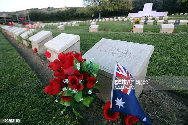 A New Zealand's flag and flowers are seen near ANZAC soldiers grave stones at ANZAC cemetery near the ANZAC cove on April 23 2015 in Canakkale before...