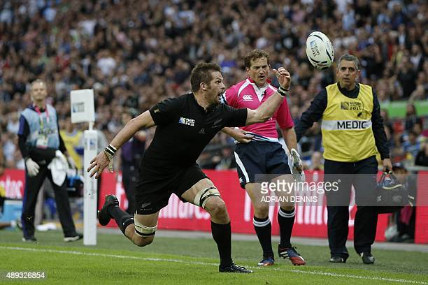 New Zealand's flanker and captain Richie McCaw reaches for the ball during a Pool C match of the 2015 Rugby World Cup between New Zealand and...