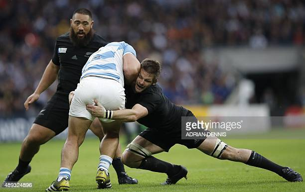 New Zealand's flanker and captain Richie McCaw tackles Argentina's hooker and captain Agustin Creevy next to New Zealand's prop Charlie Faumuina...