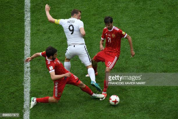TOPSHOT New Zealand's forward Chris Wood is tackled by Russia's defender Georgiy Dzhikiya and Russia's midfielder Alexander Erokhin during the 2017...