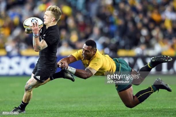 New Zealand's fullback Damian McKenzie evades a tackle by Australia's centre Samu Kerevi during the Rugby Championship test match between Australia...