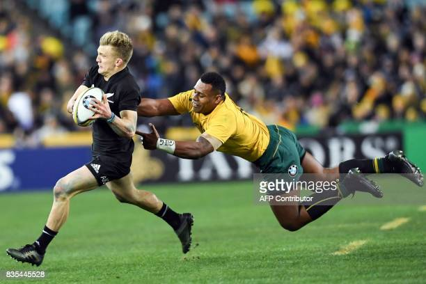 TOPSHOT New Zealand's fullback Damian McKenzie evades a tackle by Australia's centre Samu Kerevi during the Rugby Championship test match between...