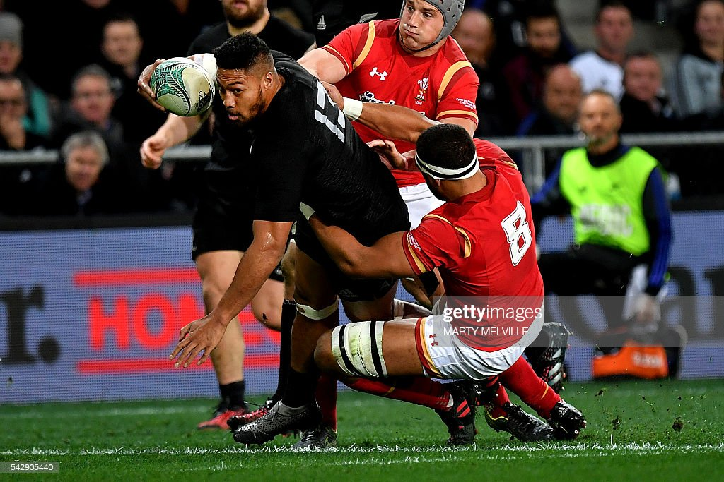 New Zealand's George Moala (L) is tackled by Luke Charteris (R) and Jonathan Davies (back R) of Wales during the third rugby union Test match between the New Zealand All Blacks and Wales at Forsyth Barr Stadium in Dunedin on June 25, 2016. / AFP / Marty Melville