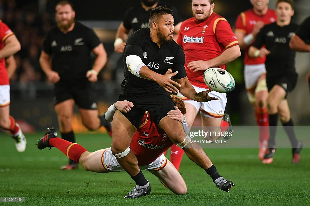 New Zealand's George Moala (C) makes a pass as he is tackled by Rhys Patchell of Wales (bottom behind) during the third rugby union Test match between the New Zealand All Blacks and Wales at Forsyth Barr Stadium in Dunedin on June 25, 2016. / AFP / Marty Melville