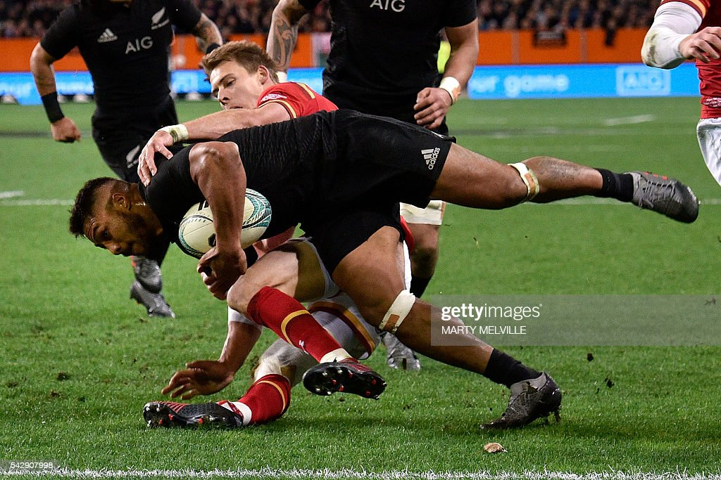 New Zealand's George Moala (bottom) scores a try as he is tackled by Liam Williams of Wales (in red) during the third rugby union Test match between the New Zealand All Blacks and Wales at Forsyth Barr Stadium in Dunedin on June 25, 2016. / AFP / Marty Melville