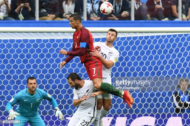 New Zealand's goalkeeper Stefan Marinovic looks on as Portugal's forward Cristiano Ronaldo heads the ball next to New Zealand's defender Andrew...