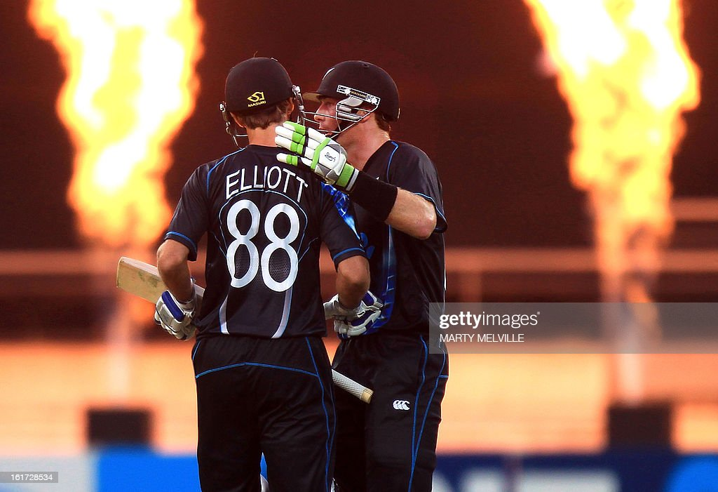 New Zealand's Grant Elliott (L) is given a pat on the back after hitting a four by team mate Martin Guptill during the International Twenty20 cricket match between New Zealand and England played at the Westpac Stadium in Wellington on February 15, 2013. AFP PHOTO / Marty MELVILLE