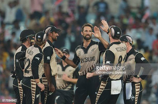 New Zealand's Grant Elliottcelebrates with teammates after the dismissal of Bangladesh's captain Mashrafe Bin Mortaza during the World T20 cricket...