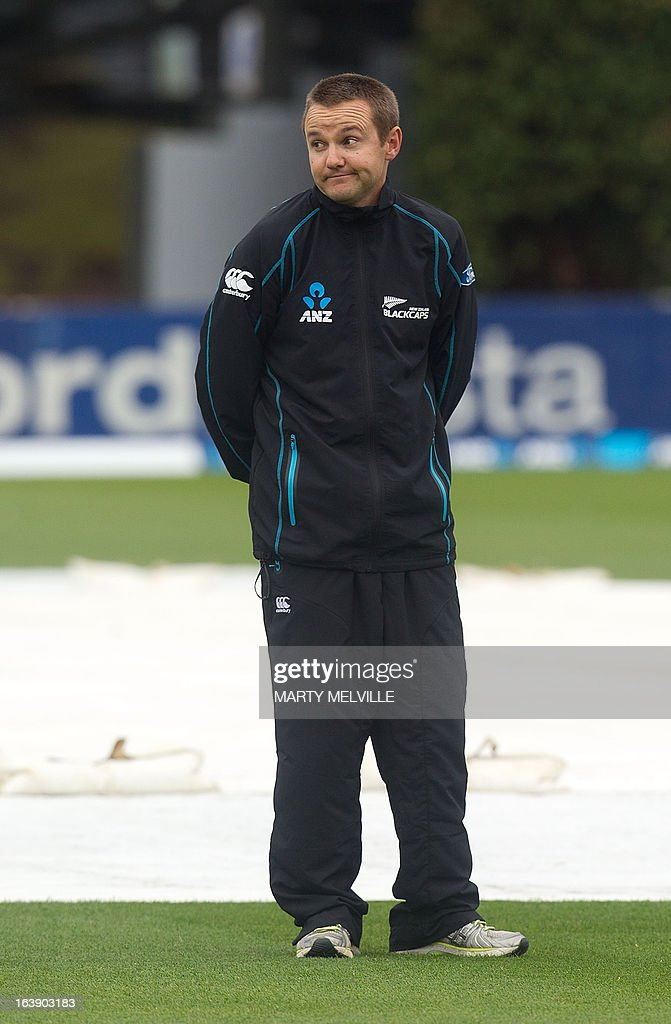 New Zealand's head coach Mike Hesson inspects the pitch as rain halts all play during day five of the international cricket Test match between New Zealand and England played at the Basin Reserve in Wellington on March 18, 2013. AFP PHOTO / Marty MELVILLE