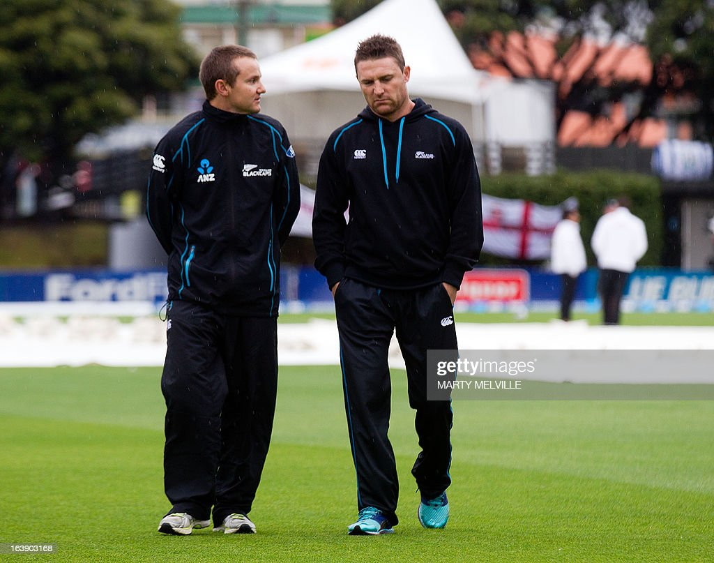 New Zealand's head coach Mike Hesson (L) walks from the field with team team captain Brendon McCullum (R) as rain halts all play during day five of the international cricket Test match between New Zealand and England played at the Basin Reserve in Wellington on March 18, 2013. AFP PHOTO / Marty MELVILLE