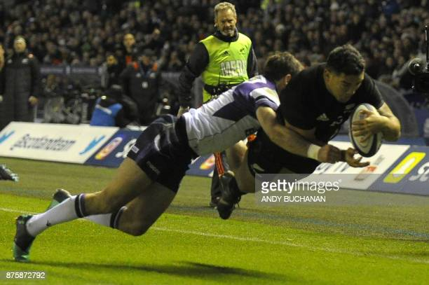 New Zealand's hooker Codie Taylor goes over the line to score the first try during the international rugby union test match between Scotland and New...