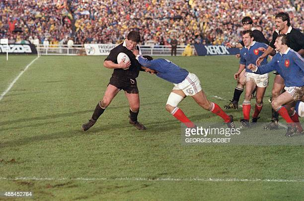New Zealand's hooker Sean Fitzpatrick tries to fend off French fullback Serge Blanco during the 1987 Rugby World Cup final match France vs New...