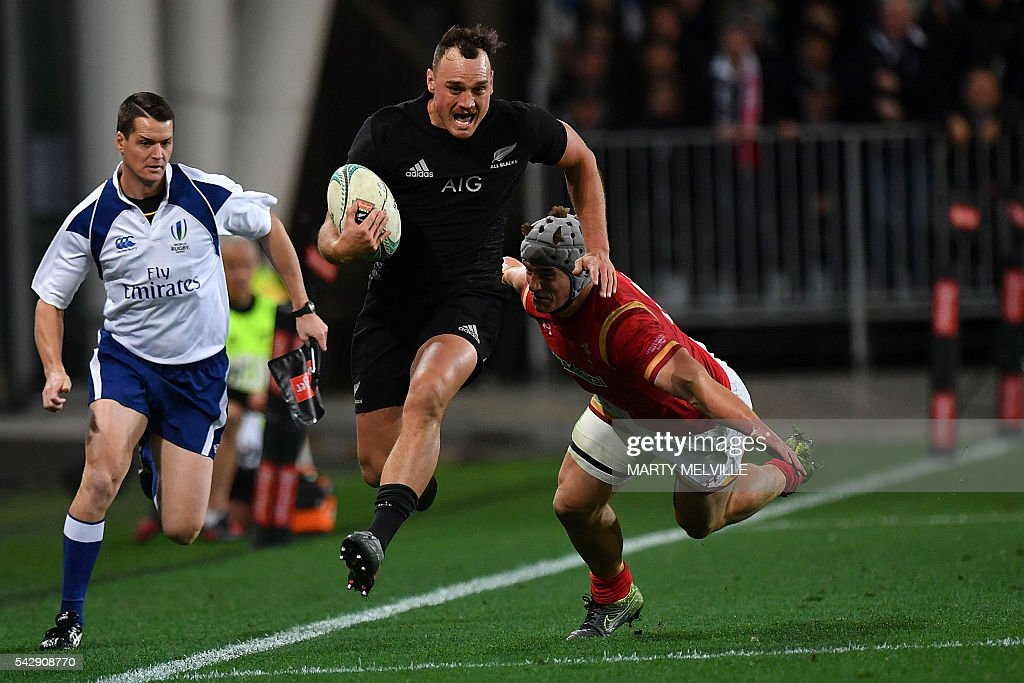 New Zealand's Israel Dagg (C) runs out of a tackle by Jonathan Davies of Wales (R) during the third rugby union Test match between the New Zealand All Blacks and Wales at Forsyth Barr Stadium in Dunedin on June 25, 2016. / AFP / Marty Melville