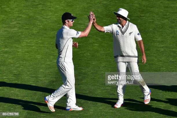 New Zealand's James Neesham celebrates with teammate Colin De Grandhomme after the dismissal of South Africa's Temba Bavuma during day two of the...