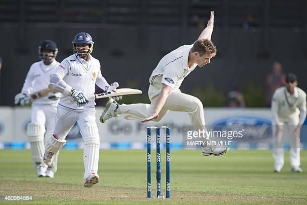 New Zealand's Jimmy Neesham jumps to take a catch as Sri Lanka's Kumar Sangakkara makes a run on day one of the second international Test cricket...