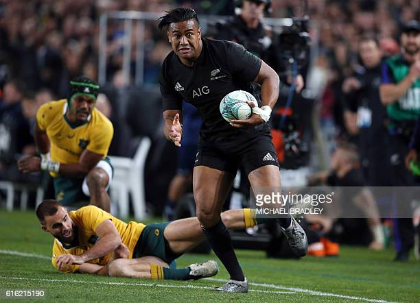 New Zealand's Julian Savea breaks the tackle from Australia's Nick Frisby and Henry Speight during the third rugby Bledisloe Cup Test between the New...