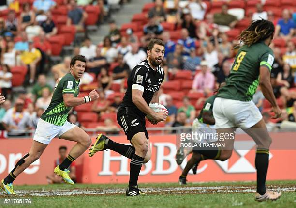 New Zealand's Kurt Baker runs past South Africa players during their cup quarterfinal match at the Singapore Sevens rugby tournament on April 17 2016...