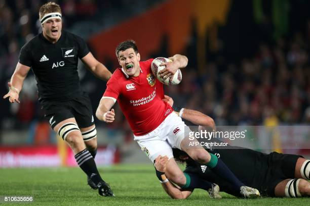 TOPSHOT New Zealand's lock Sam Whitelock tackles British and Irish Lions flyhalf Jonathan Sexton during the third rugby union Test match between the...