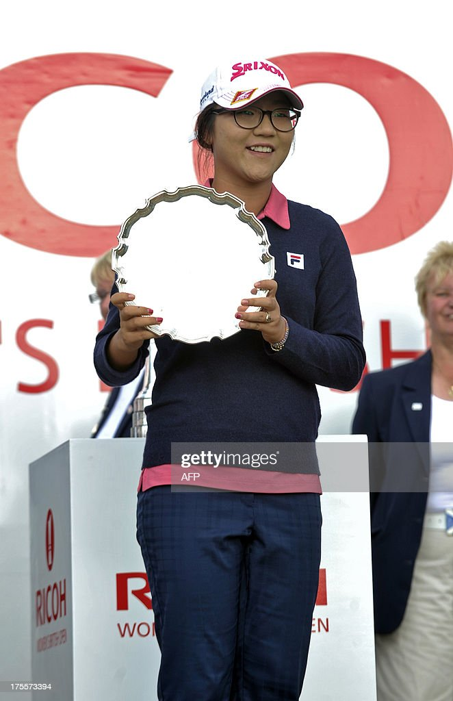 New Zealand's Lydia Ko poses with her trophy after winning the amateur title, scoring a 2 over par 294, at the Women's British Open Golf Championship at the Old Course in St Andrews, Scotland, on August 4, 2013. US golfer Stacy Lewis won the women's British Open on Sunday by two shots. Lewis, the winner of the 2011 Kraft Nabisco Championship, collected her second major with a final round 72 for an eight-under-par total of 280. AFP PHOTO/ANDY BUCHANAN