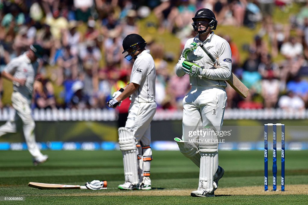 New Zealand's Martin Guptill (R) walks from the field after being caught with teammate Tom Latham (L) during day three of the first cricket Test match between New Zealand and Australia at the Basin Reserve in Wellington on February 14, 2016. AFP PHOTO / MARTY MELVILLE / AFP / Marty Melville