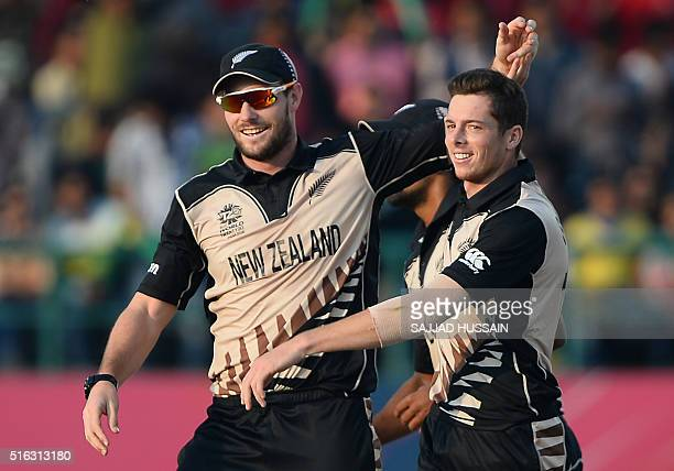 New Zealand's Mitchell Santner celebrates with teammate New Zealand's Martin Guptill after his dismissal of Australia's David Warner during the World...
