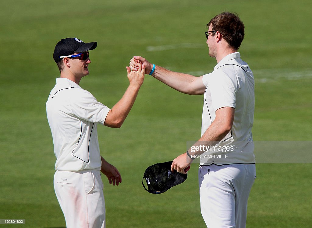 New Zealand's Neil Broom (L) and Michael Rae celebrate after England's Ian Bell was caught out during day two of the four-day warm up international cricket match between New Zealand and England in Queenstown on February 28, 2013. AFP PHOTO / Marty MELVILLE