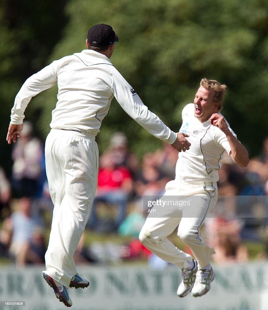 New Zealand's Neil Wagner (R) celebrates catching out England's Jonathan Trott with team mate Hamish Rutherford during day four of the first international cricket test match between New Zealand and England played at the University Oval park in Dunedin on March 10, 2013. AFP PHOTO / Marty MELVILLE