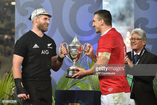 New Zealand's No 8 Kieran Read and British and Irish Lions blindside flanker Sam Warburton hold up the trophy after the drawn test series following...