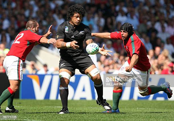 New Zealand's number 8 Sione Lauaki as Portugal's centre Diogo Mateus and Portugal's Tiago Girao try to stop him during their rugby union World Cup...