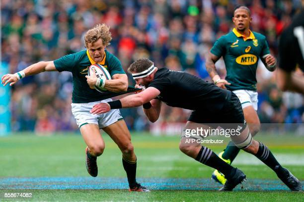 New Zealand's Number Eight Kieran Read tackles South Africa's winger Andries Coetzee during the Rugby test match between South Africa and New Zealand...