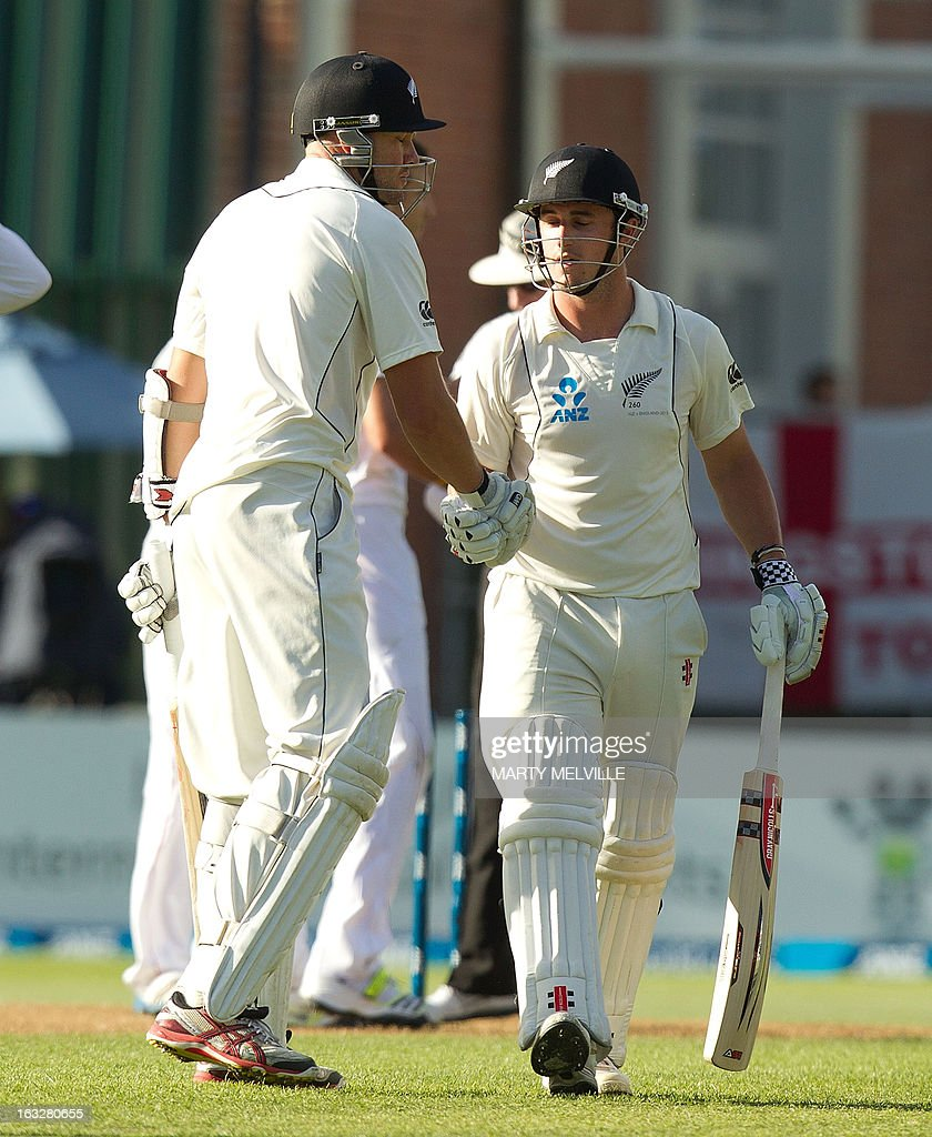 New Zealand's Peter Fulton (L) shakes hands with teammate Hamish Rutherford at the end of the days play during day two of the first international cricket Test match between New Zealand and England played at the University Oval park in Dunedin on March 7, 2013. AFP PHOTO / Marty MELVILLE