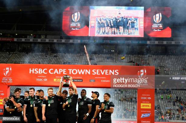 New Zealand's players celebrate with the trophy after winning the World Rugby Sevens Series at Cape Town Stadium on December 10 2017 in Cape Town /...