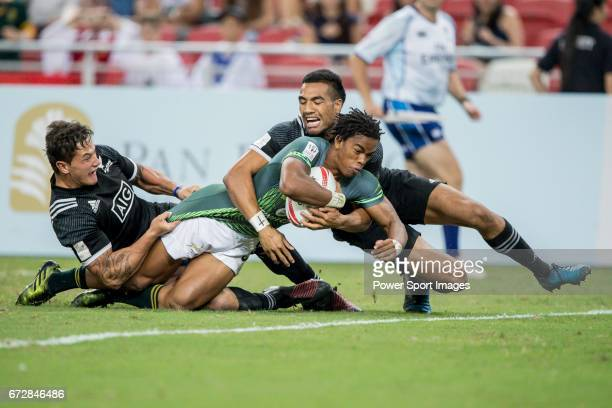 New Zealand's players tackle Tim Agaba of South Africa who has the ball during the match South Africa vs New Zealand Day 2 of the HSBC Singapore...