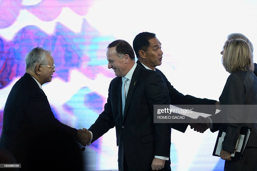 New Zealand's Prime Minister John Key (2nd L) shakes hands with Hiromasa Yonekura (L), chairman of Sumitomo Chemical Co., while Indonesia's Trade Minister Gita Wirjawan (2nd R) shakes hands with Michael Ducker (back R-hidden), chief operating officer and president of International FedEx Express, as moderator Susan Schwab (front R) looks on, after their forum, at the Asia-Pacific Economic Cooperation (APEC) CEO Summit attended by leaders of APEC member countries and top international business executives in Nusa Dua on the Indonesian resort island of Bali on October 6, 2013. Leaders of the 21-member APEC grouping are arriving in Bali ahead of the leader's summit on October 7-8.