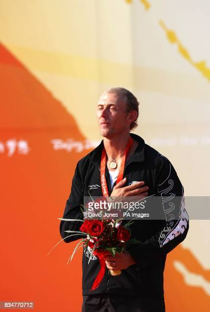 New Zealand's RSX sailor Tom Ashley hold shis hand on his heart during the national anthem after he wins Gold after the final round of his RSX...