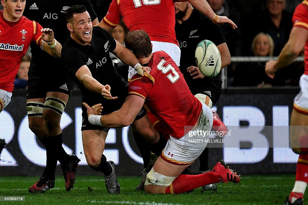 New Zealand's Ryan Crotty (2nd L) gets a pass away as he is tackled by Alun Wyn Jones of Wales (C-#5) during the third rugby union Test match between the New Zealand All Blacks and Wales at Forsyth Barr Stadium in Dunedin on June 25, 2016. / AFP / Marty Melville