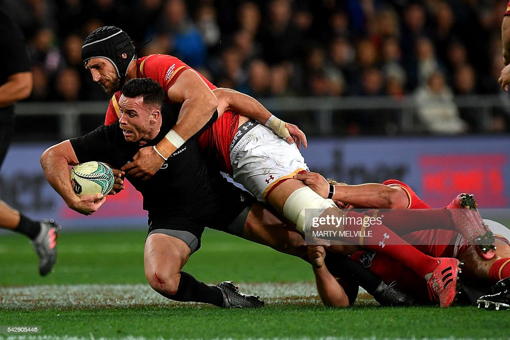 New Zealand's Ryan Crotty (bottom L) is tackled by Luke Charteris of Wales (top) during the third rugby union Test match between the New Zealand All Blacks and Wales at Forsyth Barr Stadium in Dunedin on June 25, 2016. / AFP / Marty Melville