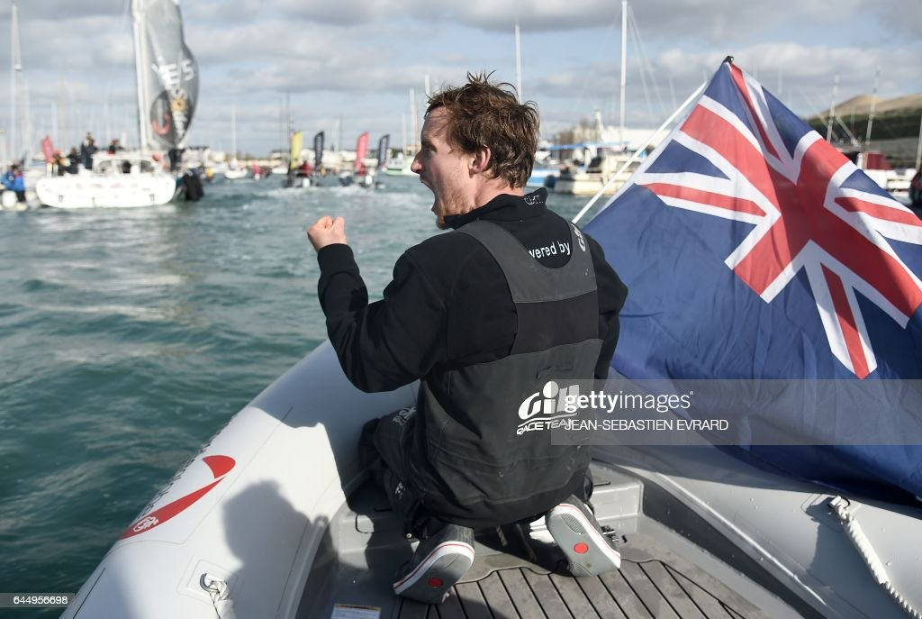 New Zealand's skipper Conrad Colman celebrates on a press boat with a New Zealand national flag after he arrived on his Imoca 60 monohull 'Foresight Natural Energy' in Les Sables-d'Olonne, western France, at the end of the Vendee Globe around-the-world solo sailing race on February 24, 2017. Colman finished 16th. /