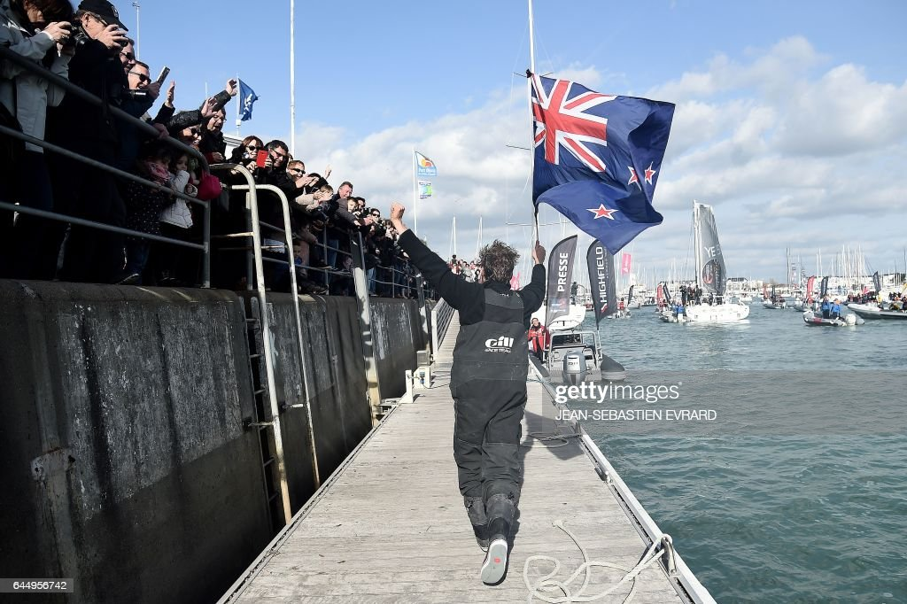 New Zealand's skipper Conrad Colman, holding a New Zealand national flag, greets supporters after he arrived on his Imoca 60 monohull 'Foresight Natural Energy' in Les Sables-d'Olonne, western France, at the end of the Vendee Globe around-the-world solo sailing race on February 24, 2017. Colman finished 16th. /