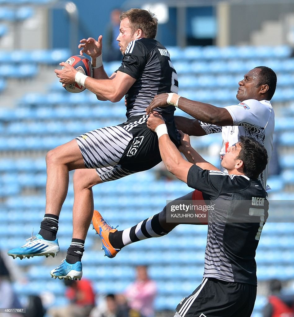 New Zealand's Tim Mikkelson (L, top) catched a line out aginst Fiji during their Tokyo Sevens 2014 Cup semi-final match, part of the Rugby Sevens World Series, in Tokyo on March 23, 2014. Fiji won the match. AFP PHOTO / KAZUHIRO NOGI