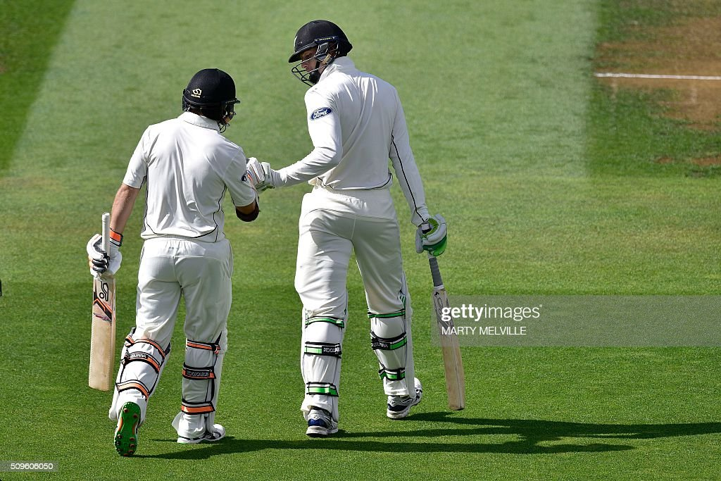 New Zealand's Tom Latham (L) and teammate Martin Guptil walk onto the filed at the start of the days play during day one of the first cricket international five-day Test match between New Zealand and Australia at Basin Reserve in Wellington on February 12, 2016. AFP PHOTO / MARTY MELVILLE / AFP / Marty Melville