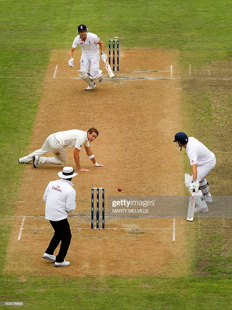 New Zealand's Trent Boult (L) drops a catch from England's Nick Compton (top) with England's captain Alastair Cook (R) and umpire Asad Rauf (bottom) during day four of the first international cricket Test match between New Zealand and England played at the University Oval park in Dunedin on March 9, 2013. AFP PHOTO / Marty MELVILLE