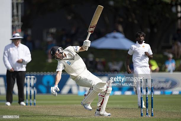 New Zealand's Trent Boult falls over after ducking a bouncer on day one of the second international Test cricket match between New Zealand and Sri...