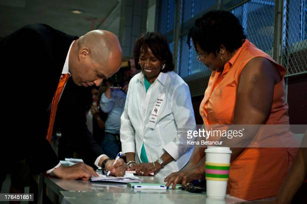 Newark Mayor and Senate candidate Cory Booker signs a paper at a polling center as he cast his vote on August 13 2013 in Newark New Jersey Voters go...