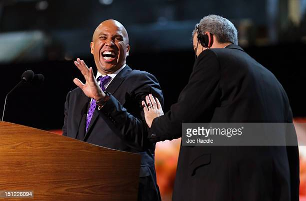 Newark Mayor Cory Booker laughs at the podium with stage manager David Cove during a walkthrough before the start of day one of the Democratic...