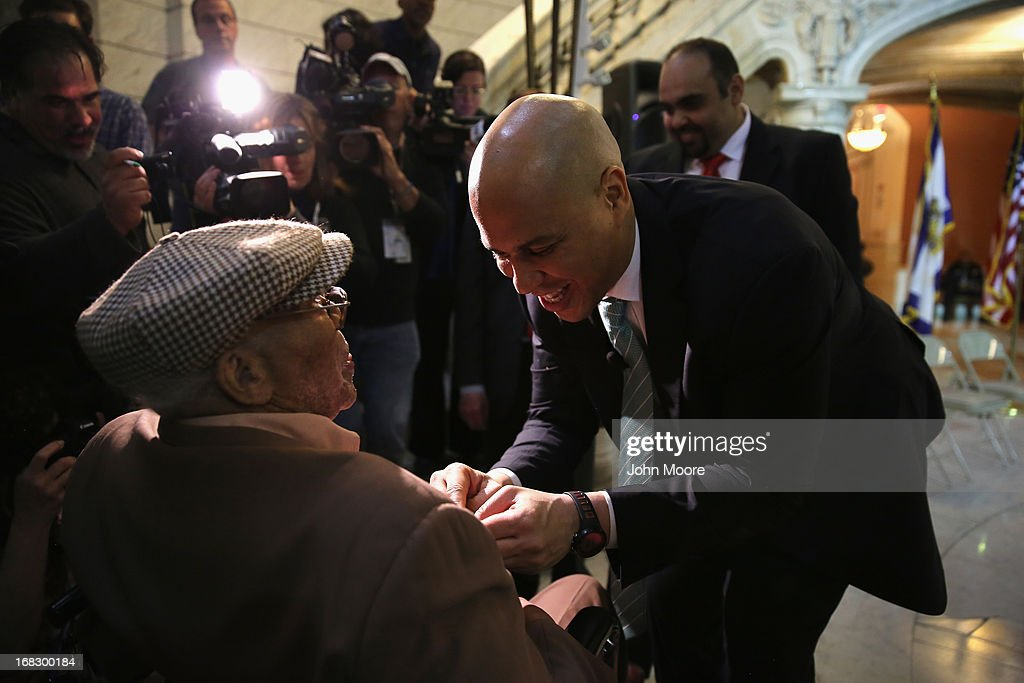 Newark Mayor Cory Booker pins New Jersey's Meritorious Service Medal onto the chest of 90-year-old WWII veteran Willie Wilkins at the Newark City Hall on May 8, 2013 in Newark, New Jersey. Booker, who has declared that he will run for New Jersey's open U.S. Senate seat in 2014, honored the 90-year-old WWII veteran on the 68th anniversary of Victory in Europe Day. At the ceremony, Wilkins received his dog tags, which were recently unearthed in a French garden, some 67 years after he lost them in France during WWII.
